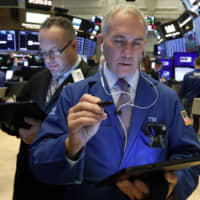 Traders Robert Arciero (left) and Timothy Nick work on the floor of the New York Stock Exchange Wednesday. Stocks are opening broadly higher as traders became more hopeful that a trade deal between the U.S. and China was making progress.
